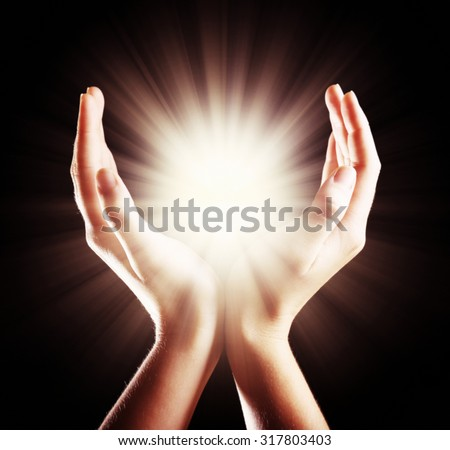 The light in young woman hands - stock photo