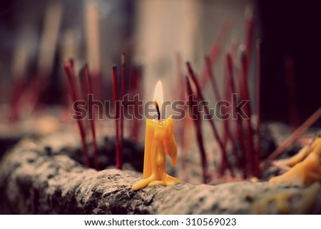 The lighted candle on joss stick pot, selected focus on the candle - stock photo