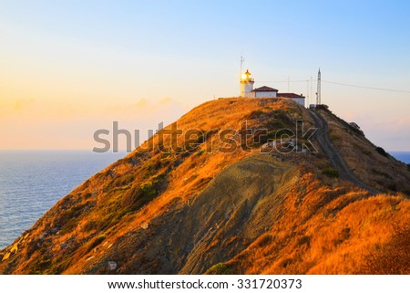 The lighthouse at Cape Emine at sunrise, Black sea coast, Bulgaria. The morning sun rays are reflected in the windows of the lighthouse - stock photo