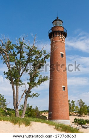 The lighthouse at Michigan's Little Sable Point  rises from sand dunes overlooking Lake Michigan. - stock photo