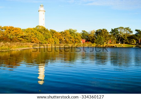 The lighthouse Long Erik situated on the northern tip of Oland, Sweden. Here seen in late afternoon in autumn. Landscape is colorful and warmed by the late sunshine. - stock photo