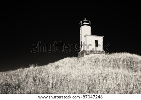 The lighthouse on Cattle Point on San Juan Island in Washington State stands on top of a small hill.  (In black and white from a camera converted to infrared.) - stock photo
