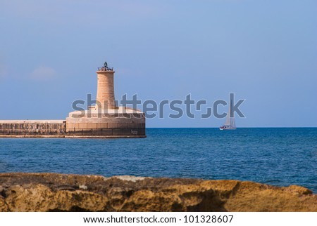 The lighthouse on the end of the Grand Harbor Breakwater seen from the opposite shore on a clear bright day. - stock photo