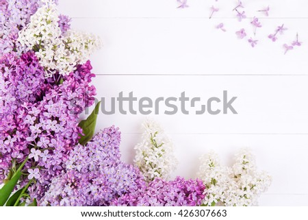 The lilac purple and white flowers on a white wooden table - stock photo