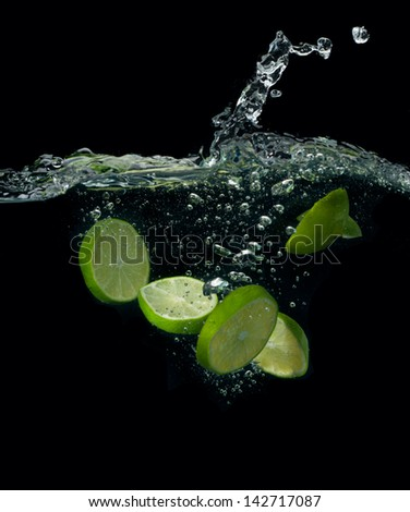 The lime slices falling into water . - stock photo