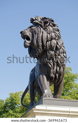 The lion sculpture topping the Maiwand war memorial on public display in Forbury Gardens, Reading, Berkshire.  It commemorates those killed in the Battle of Maiwand  in the late 19th century. - stock photo