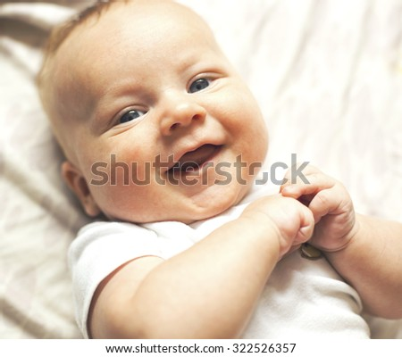 The little baby laughing lying on bed - stock photo