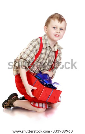 The little blonde boy in red shorts and a plaid shirt sitting on his lap. In the hands of a boy holding a big red box tied with a blue bow. The boy received his Christmas gift-Isolated on white - stock photo