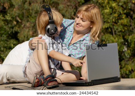 The little boy and mother with the laptop in park - stock photo