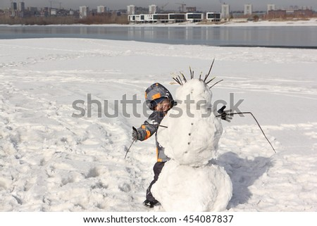 The little boy and snowman on the river bank in the winter - stock photo