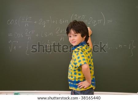 The little boy at blackboard in school - stock photo