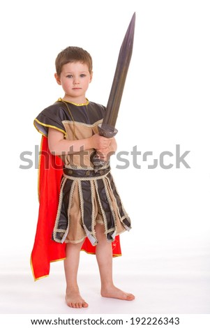 The little boy dressed as a knight holding both hands a toy sword, isolated on white background - stock photo
