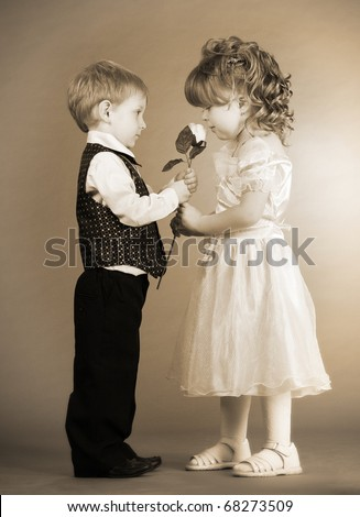 The little boy gives to the girl a flower. Old photo - stock photo