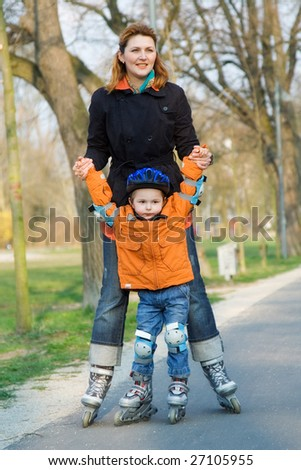 The little boy goes for a drive on rollers with mum - stock photo