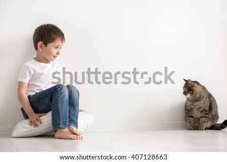 the little boy in a white undershirt plays houses with the cat - stock photo