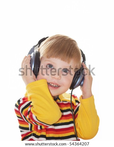 The little boy in headphones listens to music on a white background - stock photo