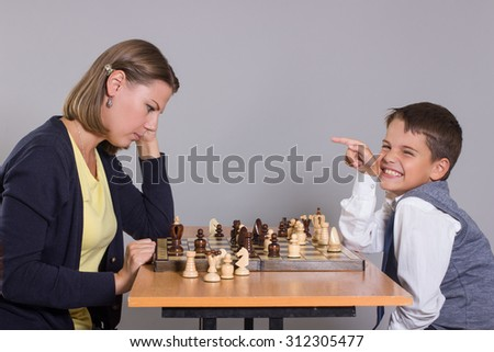 The little boy laughs with her mom playing chess. - stock photo
