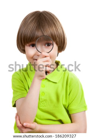 the little boy looks through a magnifying glass - stock photo