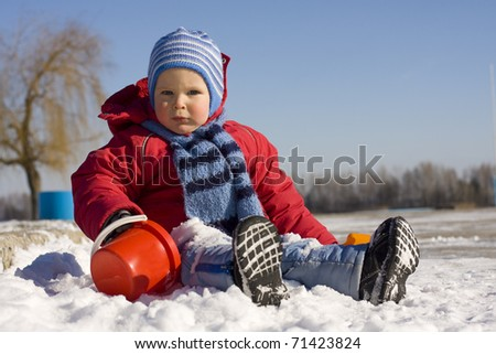 The little boy plays snow - stock photo
