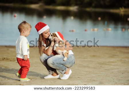 The little boy plays with puppies on the river bank - stock photo