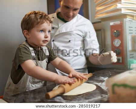 the little boy rolls pizza dough - stock photo