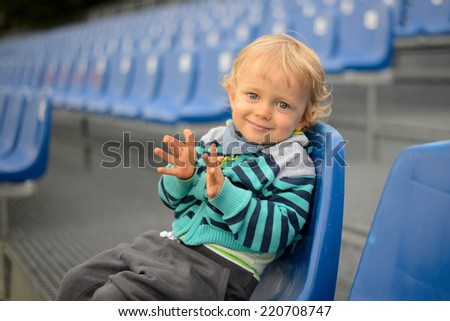 The little boy sits on a tribune  - stock photo