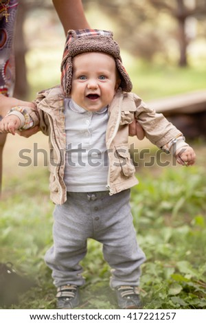 The little boy takes the first steps. His mother helps the child. Walk in the park. - stock photo