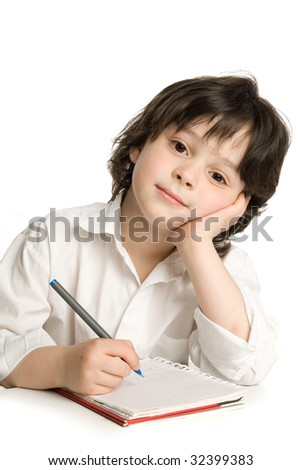 The little boy which drawing of pencil in notebook - stock photo