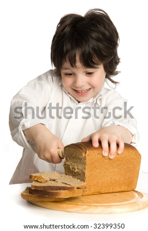 The little boy which slice a  bread on desk - stock photo