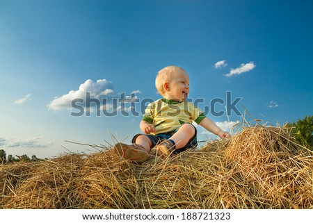 the little child smiling against the blue sky - stock photo