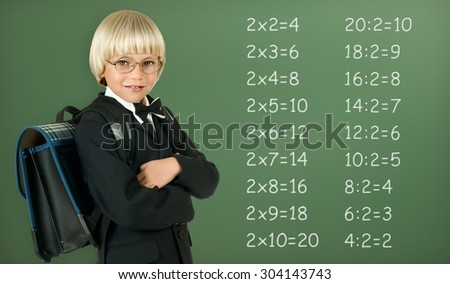 the little children schoolboy stand and smile, on green school-board background - stock photo