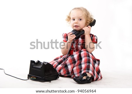 The little curly-haired blonde girl, wearing a checkered dress, talking on the old black phone, calling mom isolated on white. Retro style - stock photo
