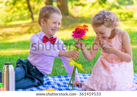 the little gentleman gives the girl a bunch of flowers - stock photo