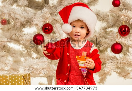 The little girl considers gifts, while celebrating Christmas at home - stock photo