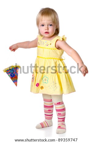 The little girl costs with a party hat in a hand. Isolated on a white background - stock photo