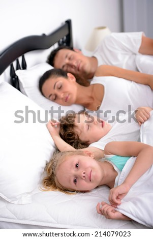 The little girl crying in bed at the time when the mother, father and brother sleep in the bedroom - stock photo