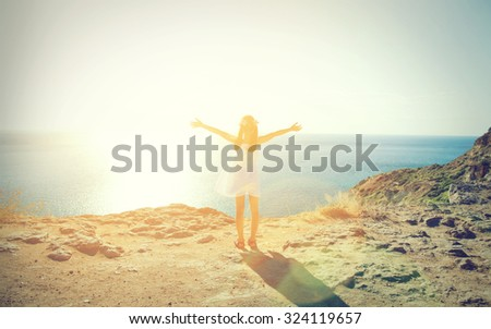 The little girl in a white dress standing on the edge of a  mountain and looking at sea - stock photo