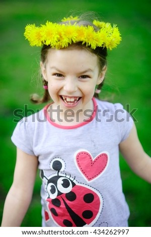The little girl in a wreath from yellow dandelions. The cheerful girl on a green background. Hair are braided in small braids. On the head a beautiful wreath. The wide smile bares large teeth. - stock photo