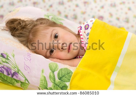 The little girl in bed. - stock photo
