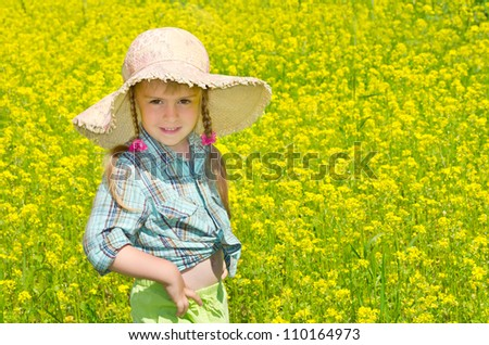 The little girl in the hat among the blossoming of the field. - stock photo