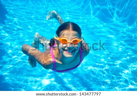 The little girl in the water park swimming underwater and smiling - stock photo