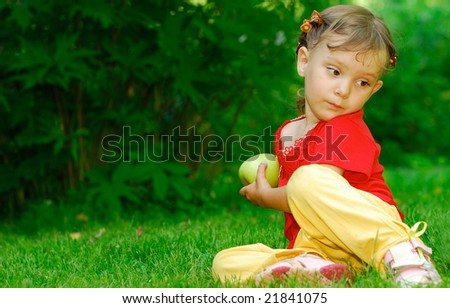 The little girl is greedy and does not give to girlfriends a green apple. - stock photo