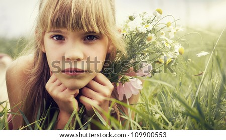 The little girl is lying in the meadow and holding the bouquet - stock photo