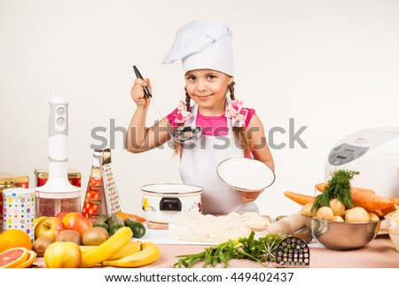 The little girl is preparing in the kitchen - stock photo