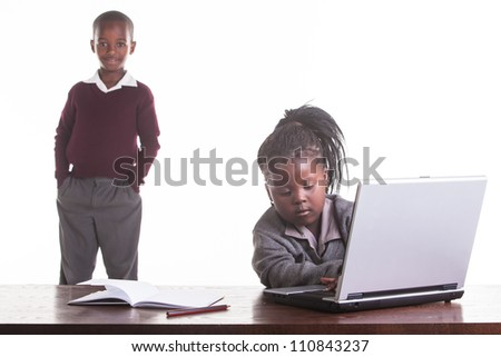 The little girl is trying to figure out how the computer works. - stock photo
