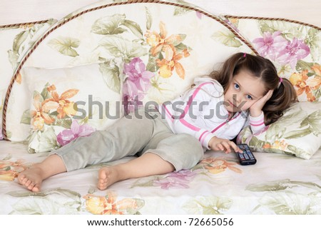 The little girl lies on a sofa and switches channels of the TV by means of a remote control - stock photo