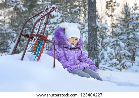 The little girl on a walk in the winter woods - stock photo