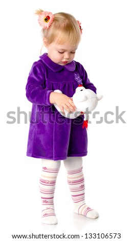 The little girl plays with a teddy bear. Isolated on a white background - stock photo