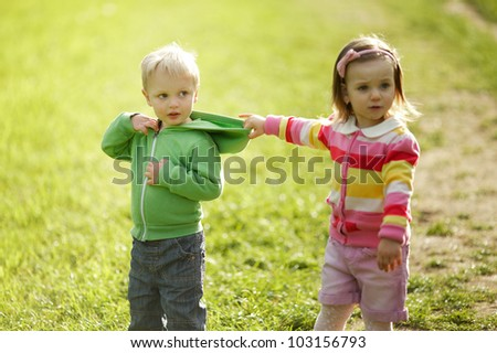 the little girl pulls the boy's hood - stock photo