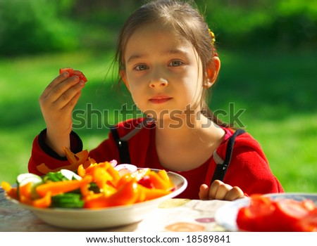 The little girl sits at a table in garden of parents and eats cut vegetables. - stock photo